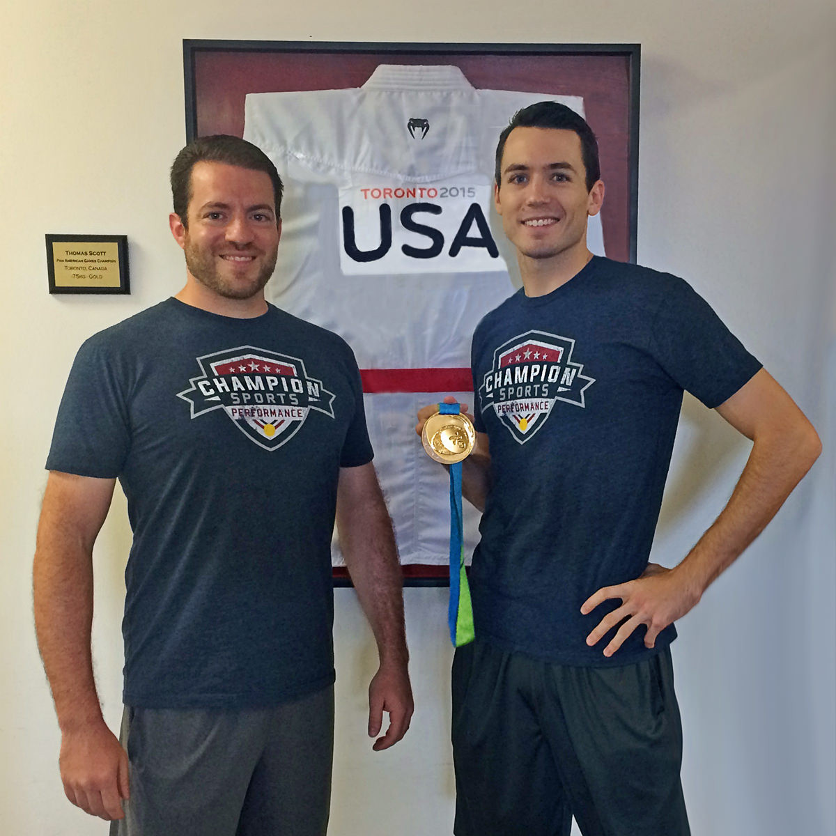 Champion Sports Performance Coach Chris Stratis and Athlete Tom Scott with his Pan American Games gold medal and his framed gi from the competition.